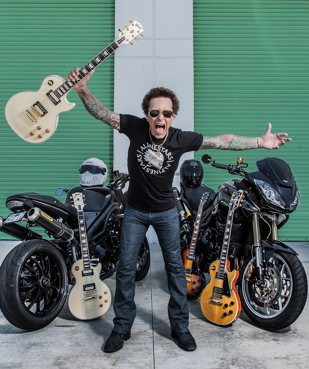 <strong>Rhythm Guitarist for Billy Idol, Billy Morrison:</strong> Billy Morrison's father raced in the Isle of Man TT and his uncle was a grand prix racer, so the apple doesn't fall too far from the tree in terms of being a motorcycle enthusiast. Here Morrison is posing with two of his main passions, motorcycles and guitars.