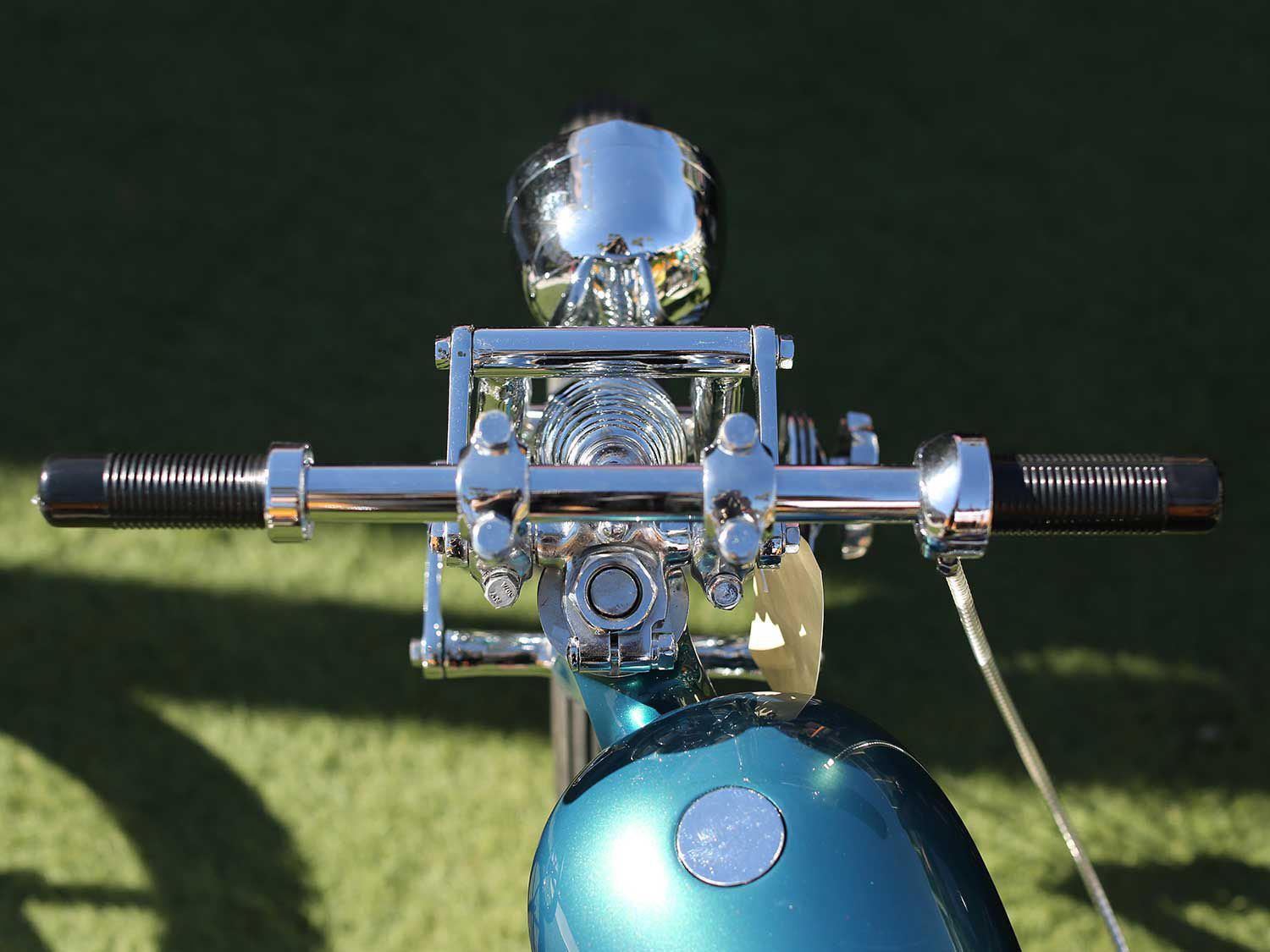 A clean and polished handlebar and front end setup on this skinny Panhead chopper.