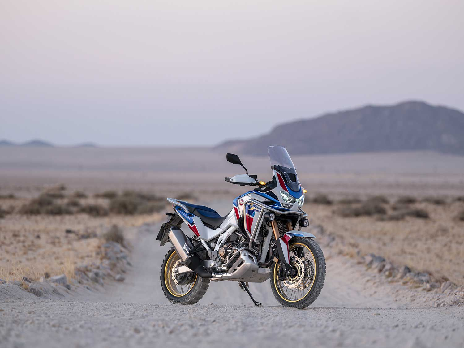 Evoking the purposeful style and stance of the Dakar Rally bikes, Honda's Africa Twin Adventure Sports ES leads visually with its big 21-inch front wheel and tall fairing and windshield.