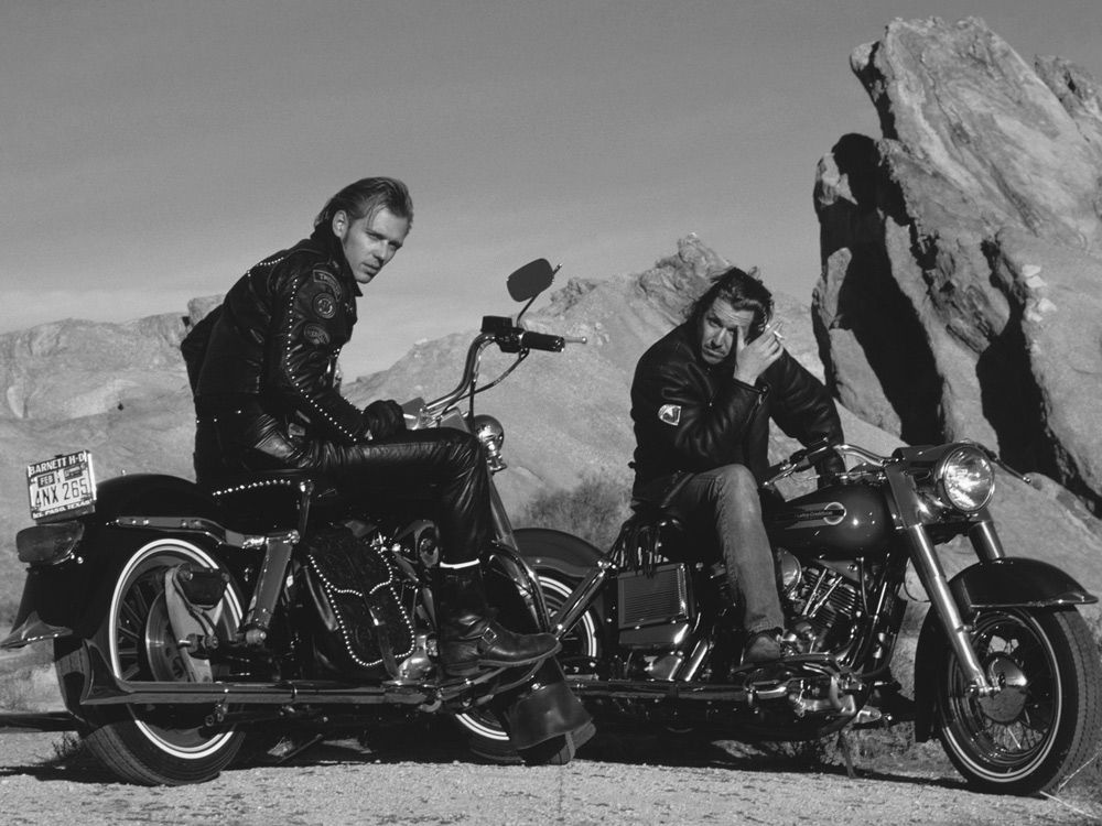 """<strong>Sex Pistols Guitarist Steve Jones and The Clash Bassist Paul Simonon:</strong> In a <a    href=""""https://www.cycleworld.com/talking-motorcycles-music-and-mayhem-with-sex-pistols-guitarist-steve-jones/""""><em>Cycle World</em> interview</a>, Jonesy """"started out stealing Vespas and Lambrettas when [he] was 11"""" and at """"16 or 17, signed some papers, and just took the bike, a Honda 650 with the four pipes."""" Later he stated that """"There was nothing like it, catching the California motorcycle bug."""" This image is of Clash bassist Paul Simonon (left) and Jones on Harleys in the late '80s."""